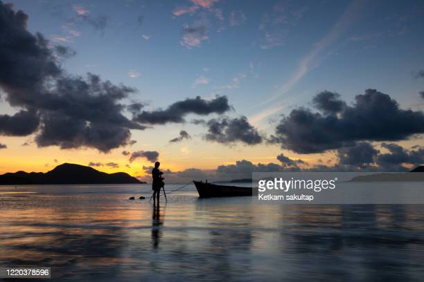 photographer is photographing  thai long tail boat at sunrise with low tide rawai beach. - インド洋 ストックフォトと画像
