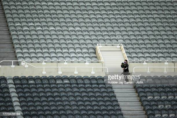 A photographer is seen in an empty stand as the match is played behind closed doors during the FA Cup Quarter Final match between Newcastle United...