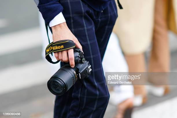 Photographer is seen wearing blue checked pants, and using a Nikon DSLR camera equipped with a Zoom lens, on October 03, 2020 in Paris, France.