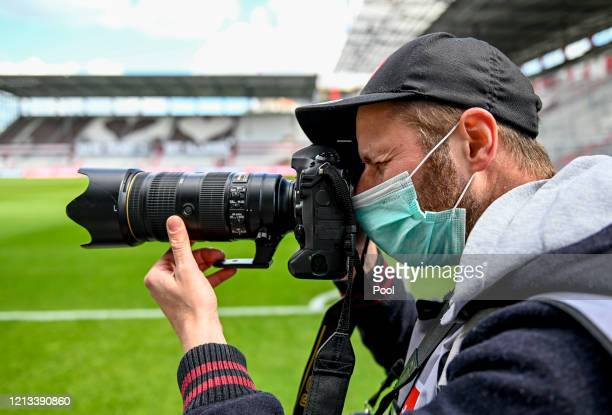Photographer is seen working inside the stadium with a protective face mask prior to the Second Bundesliga match between FC St. Pauli and 1. FC...