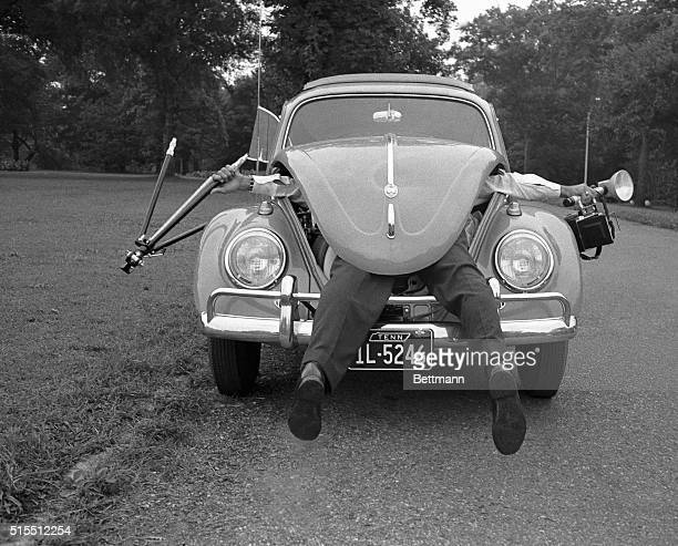 A photographer is shown with his feet sticking out of the front area of a Volkswagen Beetle In his hands sticking out to the sides are a tripod and a...
