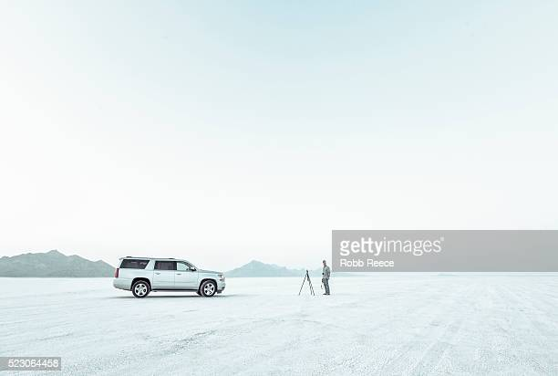 a photographer is standing next to a chevrolet suburban at bonneville salt flats, utah - robb reece stock pictures, royalty-free photos & images