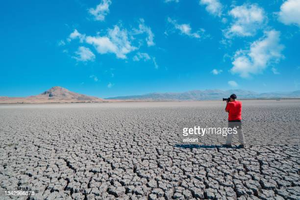 photographer is taking photos on dried cracked drought lakebed surface - greenpeace stock pictures, royalty-free photos & images