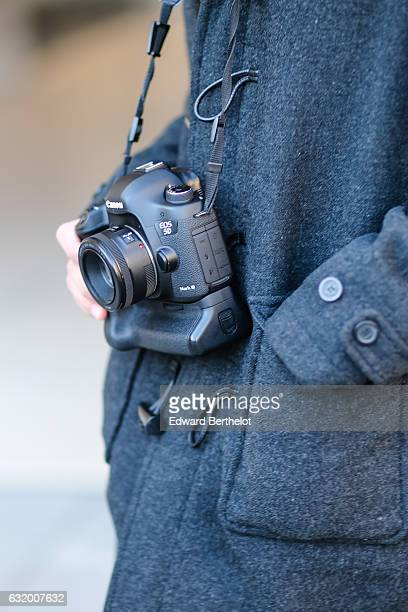 A photographer is using a Canon 5D mark iii full frame camera with a battery grip and a Canon 50mm F 18 prime lens after the Balenciaga show during...