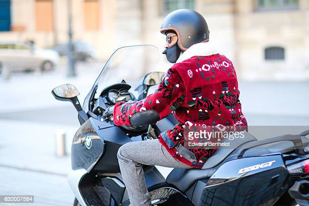 A photographer is wearing a red coat gray pants and is riding a BMW motorbike after the Balenciaga show during Paris Fashion Week Menswear...