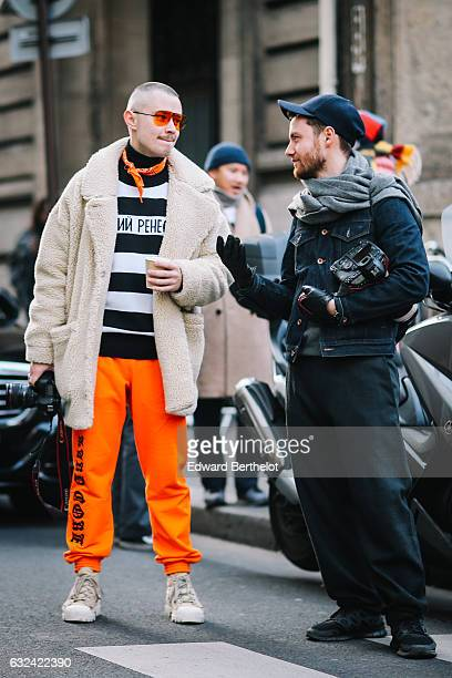 A photographer is wearing red sunglasses a white faux fur coat an orange bandanna a black and white striped top orange pants and shoes and is using a...
