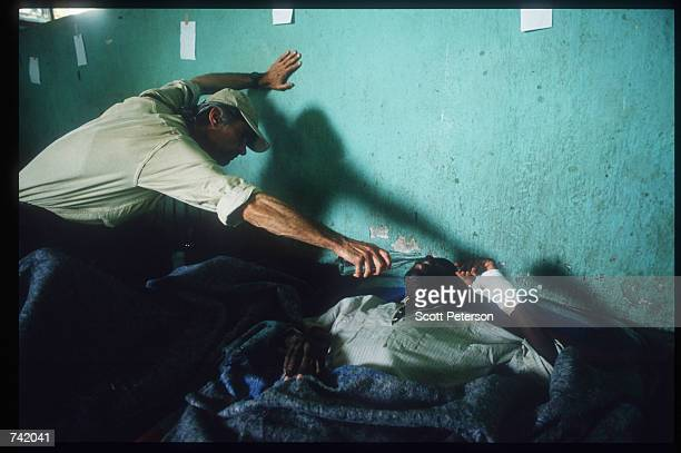 Photographer James Nachtwey of Time Magazine offers water to unidentified man June 1994 in Rwanda Wellknown journalists descended on Rwanda during...