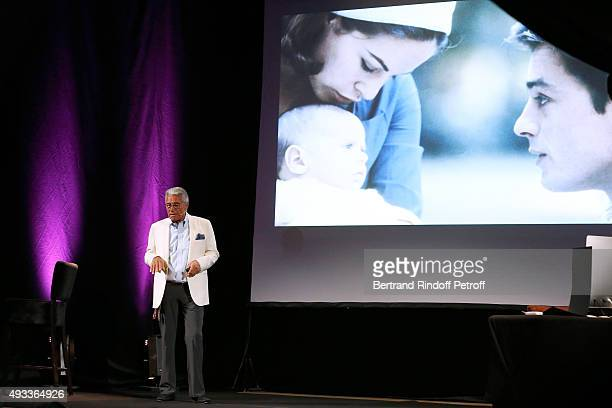 Photographer JeanMarie Perier performs in front of a pictures of Nathalie and Alain Delon during his 'FlashBack' One Man Show at Theatre de la...