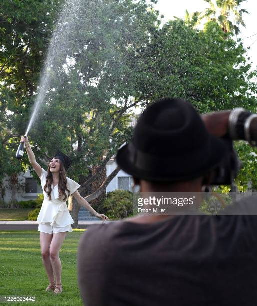 Photographer Jerry Metellus takes commencement pictures of College of William & Mary graduate Julia Carlson spraying champagne in a park across from...