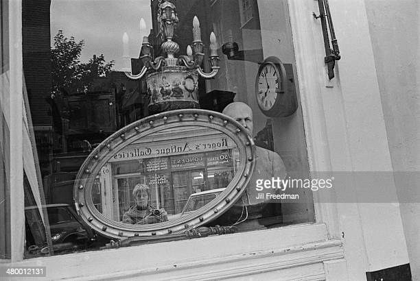 Photographer Jill Freedman reflected in a mirror in an antique shop on Portobello Road London England 1969