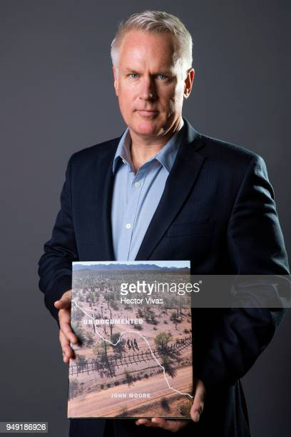 Photographer John Moore poses with his book Undocumented during the launch event of Undocumented book at WeWork Varsovia Building on April 19 2018 in...