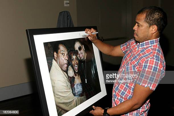 Photographer Johnny Nunez signs one of his photographs at the BET Music Matters 'Press Play' event Powered by Monster at TWELVE Atlantic Station on...