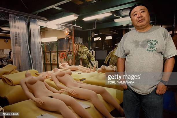 Photographer Kyoichi Tsuzuki stands beside a lifelike female doll at the Erotopia Japan exhibition in Tokyo on July 28 2016 The sex exhibition smack...