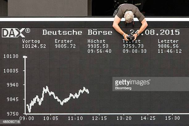 A photographer leans over an electronic boards displaying the DAX Index curve at the Frankfurt Stock Exchange in Frankfurt Germany on Monday Aug 24...