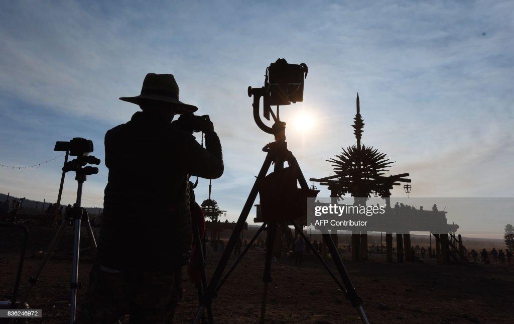 TOPSHOT - A photographer lines up his shot ahead of the total solar eclipse at Big Summit Prairie ranch in Oregon's Ochoco National Forest near the city of Mitchell on August 21, 2017. Skygazers across the United States awoke in excited anticipation Monday of witnessing the Sun briefly disappear, with the first total solar eclipse in 99 years to cast a shadow on the entire continent just hours away. / AFP PHOTO / Robyn Beck