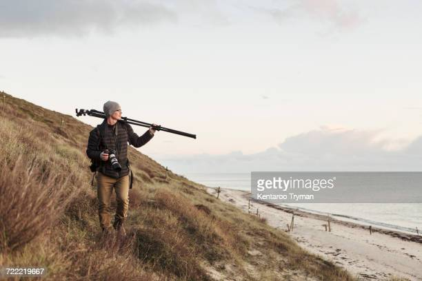 Photographer looking away while carrying tripod on hill by sea