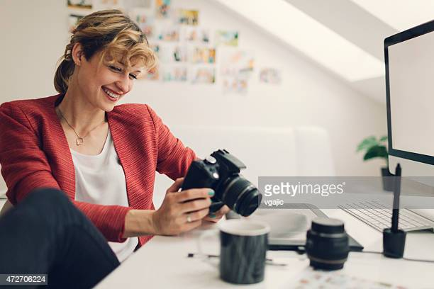 Photographer Looking Images on her Digital Camera.