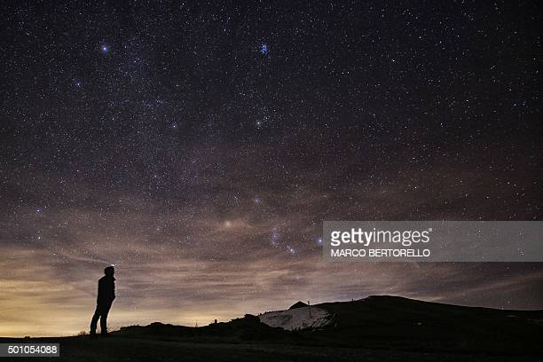Photographer looks at the sky at night to see the annual Geminid meteor shower on the Elva Hill, in Maira Valley, near Cuneo, northern Italy on...
