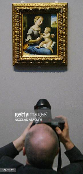A photographer makes a picture of the Madonna of the Pinks painted by Raphael at the Nationa Gallery in London 13 February 2004 The gallery and the...