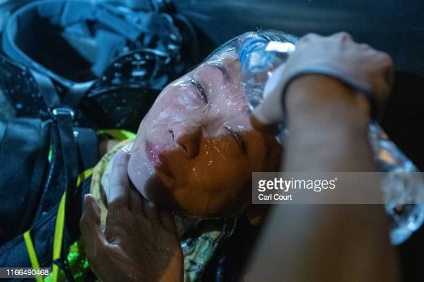 A photographer May James has water poured onto her face after being hit with pepper spray during a demonstration on September 7 2019 in Hong Kong...
