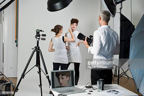 a photographer, model and make-up artist on set of a fashion shoot - fotosession stock-fotos und bilder