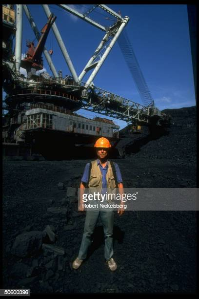 TIME photographer Nickelsberg framed by open pit coal mine extracting machinery in motion at huge mining op in Central Steppes region Ekibastuz