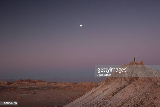 a photographer on a mountain at moonrise. - alex saberi stock pictures, royalty-free photos & images