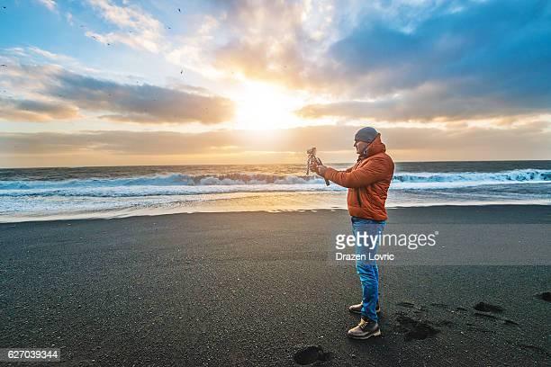 Photographer on Reynisfjara beach - black sand beach, Vik, Iceland