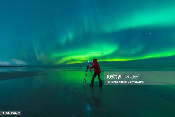 photographer on skagsanden beach during northern lights, norway - fotógrafo fotografías e imágenes de stock