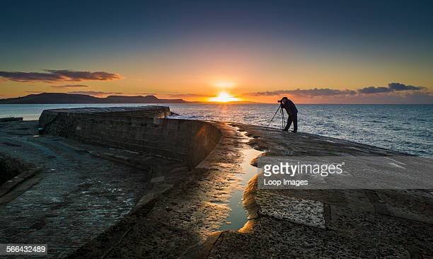 A photographer on the Cobb at Lyme Regis at dawn