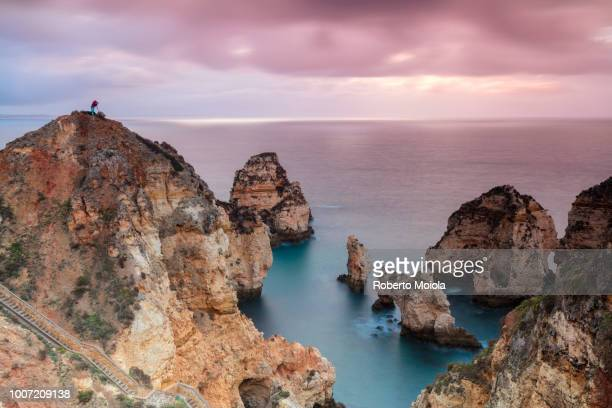 Photographer on top of cliffs surrounded by sea under the pink sky at sunrise, Ponta Da Piedade, Lagos, Algarve, Portugal, Europe