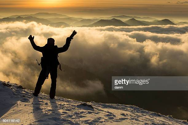 Photographer on top of mountain over the clouds enjoying the view.