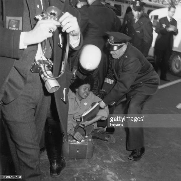 Photographer passes police officers as they attempt to lift a woman sitting on the floor during a civil rights demonstration in front of the White...