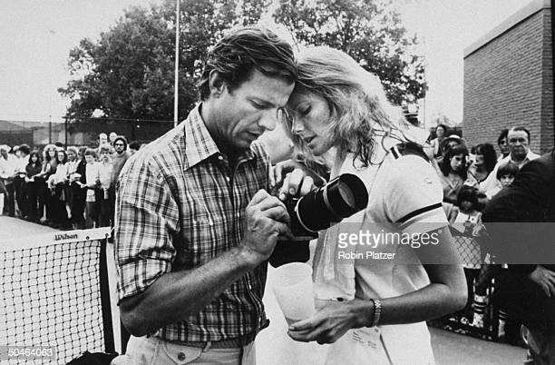 Photographer Peter Beard holding camera w model/wife Cheryl Tiegs on tennis court as crowd watches behind fence