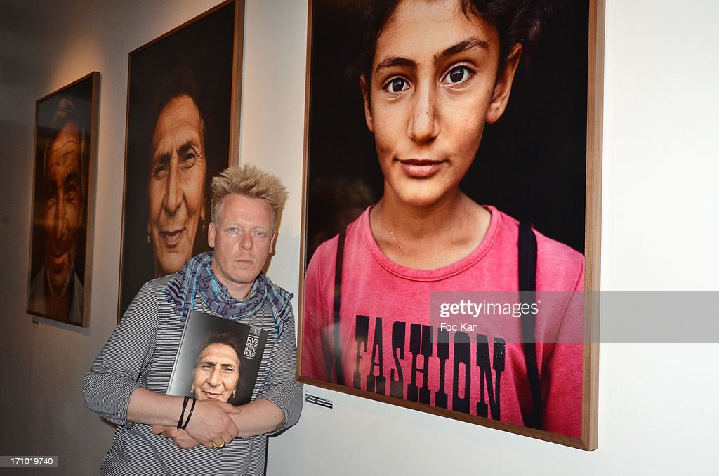 Photographer Philipp Rathmer poses with his work (portraits of refugees in Azerbaijan) during the 'Five Roads Back Home' Philipp Rathmer Photo Exhibition Preview at Galerie Joseph on June 20, 2013 in Paris, France.