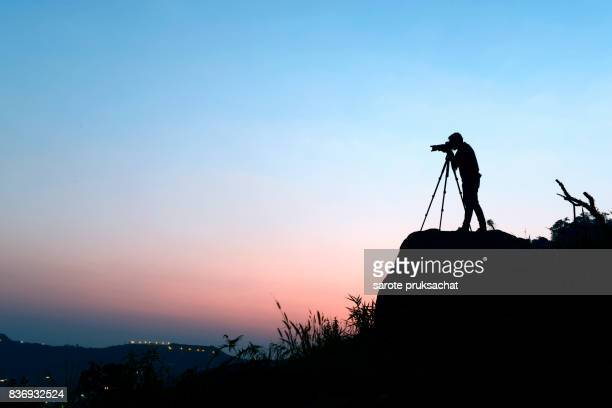 photographer .photographer take photo ,silhouette of photographer taking photo in the mountain and sunset . - film crew stock pictures, royalty-free photos & images