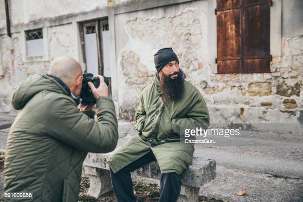 Photographer Photographing Adult Homeless Man