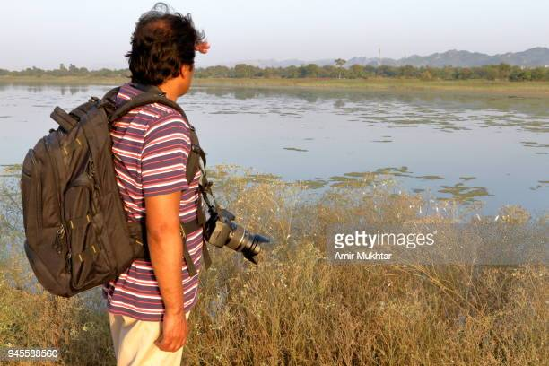 a photographer photographing and wearing backpack at lake - amir mukhtar stock photos and pictures