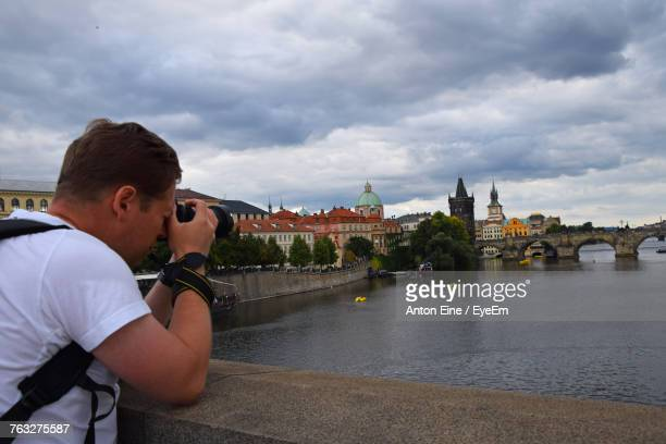 photographer photographing bridge while leaning on railing against cloudy sky - eine person stock pictures, royalty-free photos & images