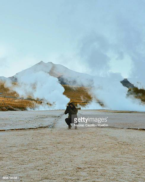 Photographer Photographing By Geyser And Mountain Against Clear Sky At El Tatio
