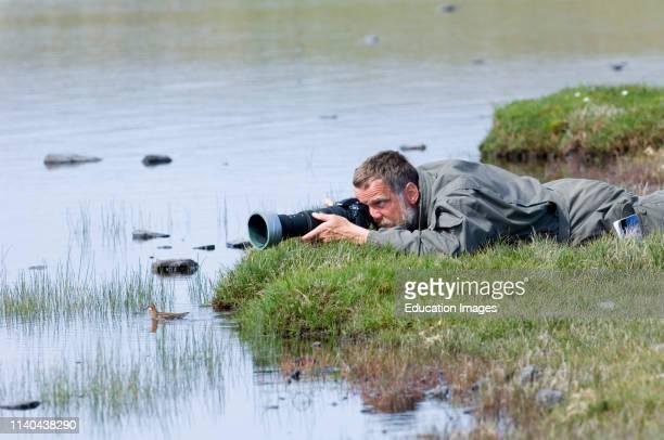 Photographer photographing Rednecked Phalaropes on Loch Funzie Fetlar Shetland