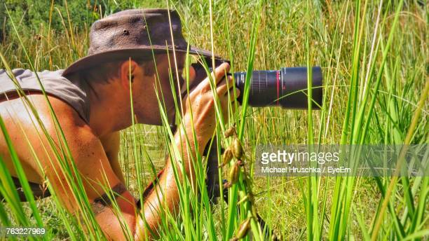 Photographer Photographing Through Camera While Lying On Grassy Field