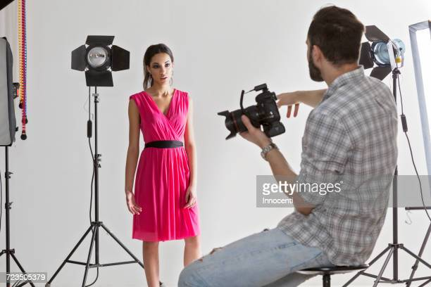 Photographer pointing at model in white backdrop photography studio shoot