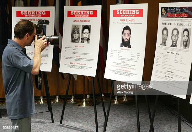 A photographer points his camera at posters of suspected alQaeda cooperatives who are seeking by the FBI prior to a news conference at the FBI...