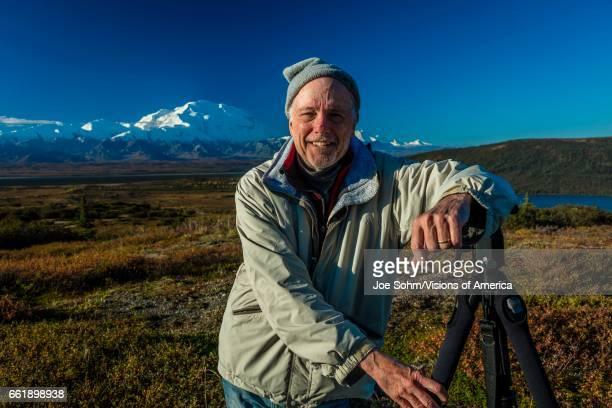 Photographer poses at famous Ansel Adams picture spot Wonder Lake Mount Denali Kantishna Alaska