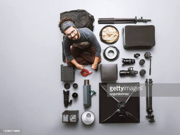photographer posing with his cameras and photographic studio equipments - photography themes stock pictures, royalty-free photos & images