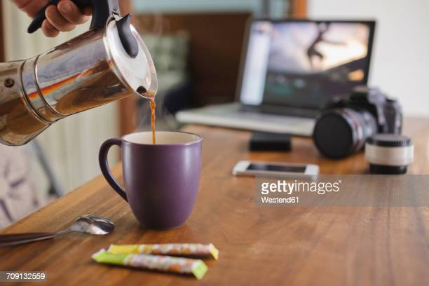 Photographer pouring coffee into cup at desk at home