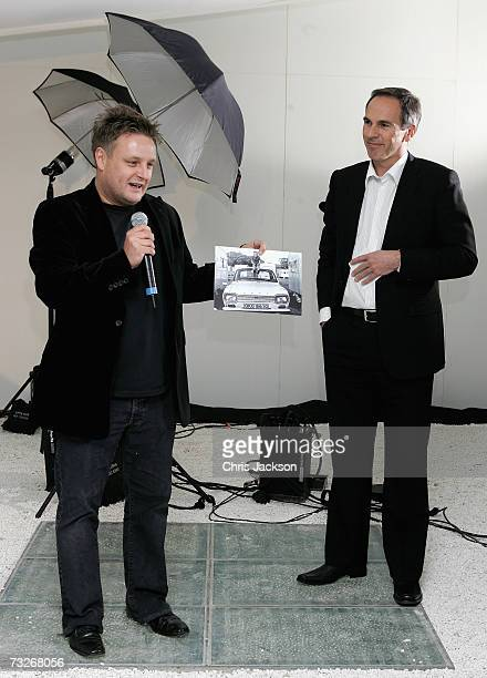 Photographer Rankin holds up a picture of himself as a young boy sitting on a Ford next to Roelant de Waard at the private viewing of ''Ford Motor...