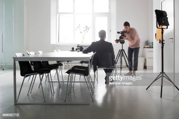 photographer recording interview of businessman in board room - filmen stockfoto's en -beelden