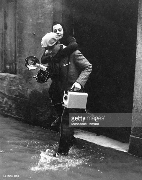 A photographer rescuing woman in a flooded street of Florence Florence November 1966
